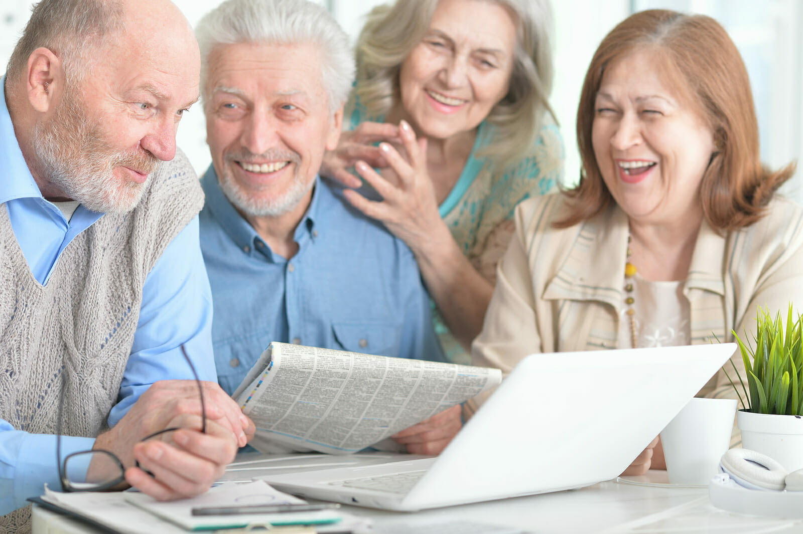Two Senior Couples Sitting At Table And Working With Laptop